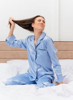 Belle jeune femme en pyjama bleu assise sur le lit touchant ses cheveux avec une expression agacée à l'intérieur de la chambre