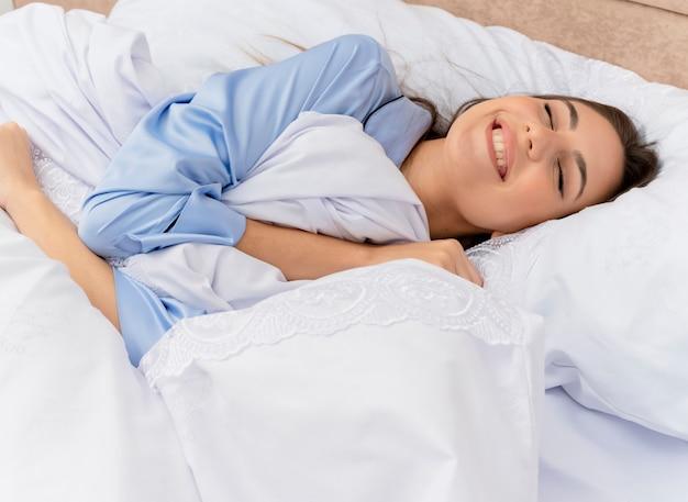 Belle jeune femme en pyjama bleu portant sur le lit reposant sur des oreillers moelleux profitant de l'heure du matin souriant avec les yeux fermés à l'intérieur de la chambre sur fond clair