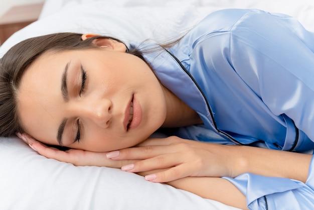 Belle jeune femme en pyjama bleu portant sur le lit