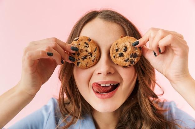 Belle jeune femme en pyjama debout isolé sur fond rose, manger des biscuits au chocolat