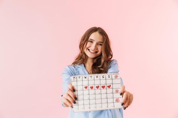 Belle jeune femme en pyjama debout isolé sur fond rose, montrant le calendrier menstruel