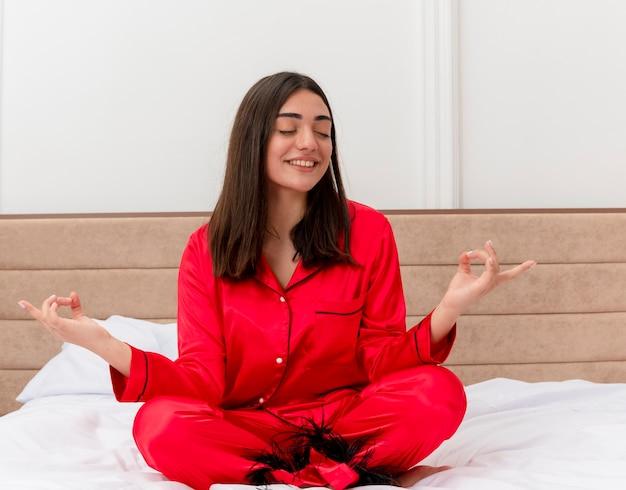 Belle jeune femme en pyjama rouge assis sur le lit de détente avec les yeux fermés faisant le geste de méditation avec les doigts dans l'intérieur de la chambre sur fond clair