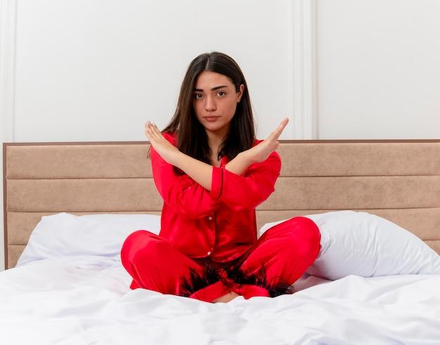 Belle jeune femme en pyjama rouge assise sur le lit faisant un geste d'arrêt croisant les mains avec un visage sérieux à l'intérieur de la chambre