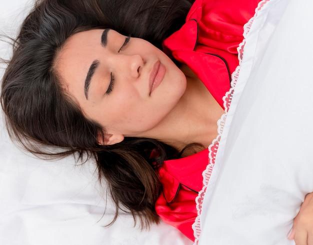 Belle jeune femme en pyjama rouge se détendre dans son lit