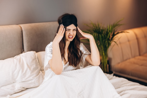 Belle jeune femme en pyjama de soie blanche avec maux de tête dans la chambre sur le lit. femme tenant sa tête alors qu'elle était assise sur le lit. matin ou soir dans la chambre avec un modèle féminin.