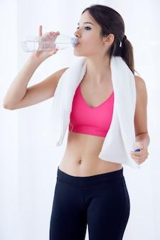 Belle jeune femme qui boit de l'eau après un entraînement à la maison.