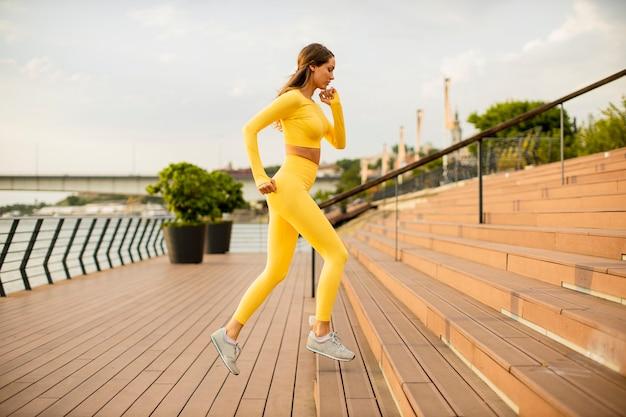 Belle jeune femme qui court dans les escaliers au bord de la rivière
