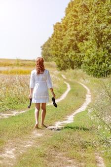 Belle jeune femme qui court dans l'herbe aux pieds nus et tenant des chaussures dans les mains