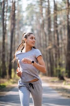 Belle jeune femme qui court dans un parc verdoyant sur une journée d'été ensoleillée