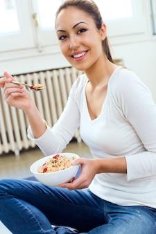 Belle jeune femme qui mange des céréales à la maison.