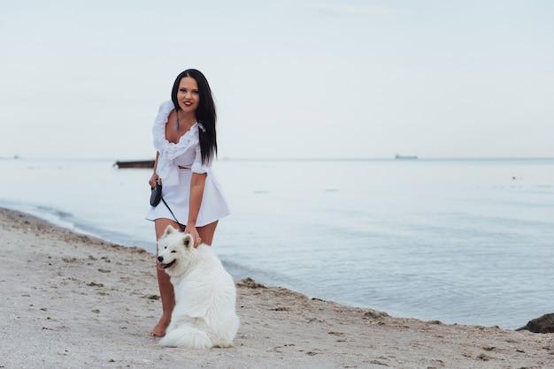 Belle jeune femme qui marche avec son chien sur la plage
