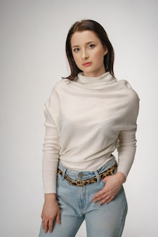 Belle jeune femme qui pose en jeans sur fond blanc