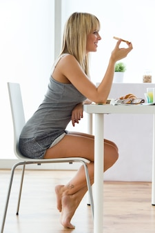 Belle jeune femme qui profite du petit-déjeuner dans la cuisine.