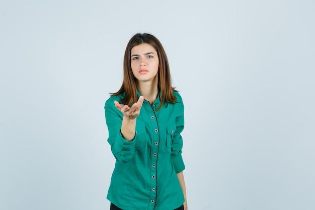 Belle jeune femme qui s'étend de la main dans le geste de questionnement en chemise verte et à la perplexité, vue de face.