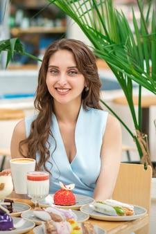Une belle jeune femme de race blanche assise à la table avec des gâteaux et une tasse de café au café en plein air
