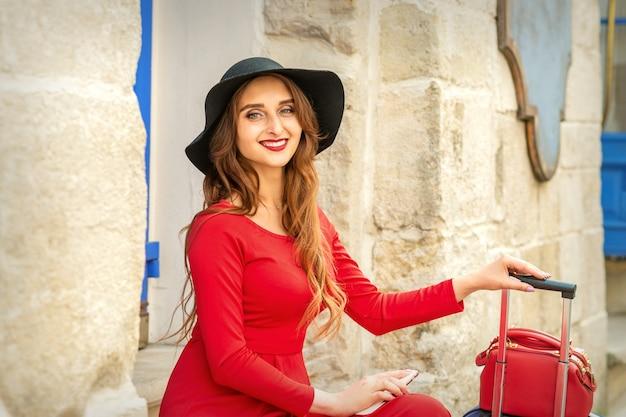 Belle jeune femme de race blanche au chapeau noir souriant et assis dans les escaliers à la porte à l'extérieur