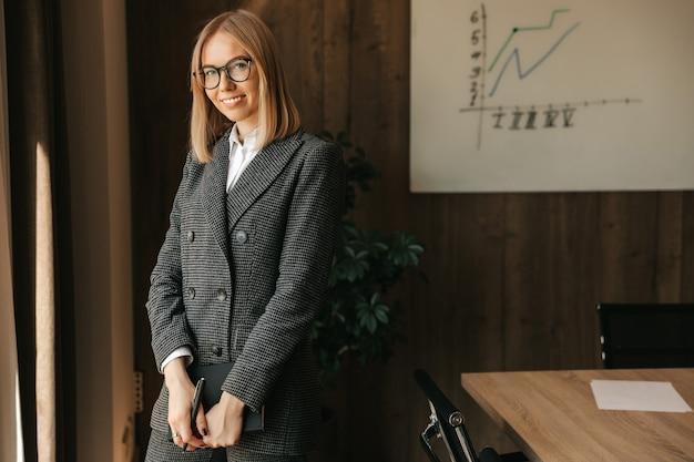Une belle jeune femme de race blanche à lunettes dans un costume et une chemise se tient près d'un bureau, tenant un cahier dans ses mains et souriant avec un sourire à pleines dents dans le bureau.
