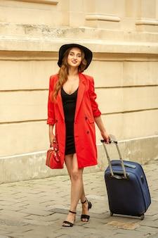 Une belle jeune femme de race blanche marche avec une valise sur une vieille rue de la ville