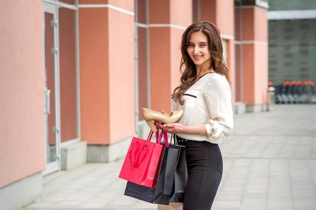 Belle jeune femme de race blanche montrant des chaussures à talons modernes debout près du centre commercial