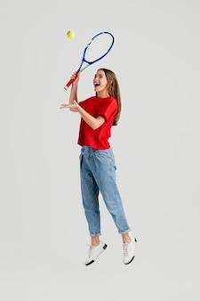Belle jeune femme avec une raquette de tennis sautant