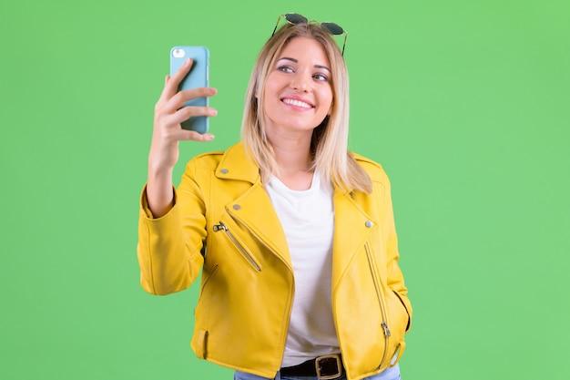 Belle jeune femme rebelle aux cheveux blonds sur clé chroma sur vert