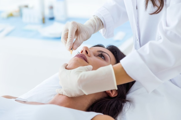 Belle jeune femme recevant une injection cosmétique de botox dans son visage.