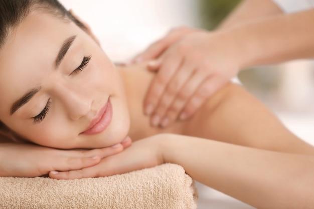 Belle jeune femme recevant un massage dans un salon spa, gros plan