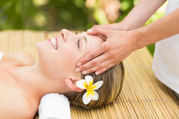 Belle jeune femme recevant un massage du visage au centre de spa