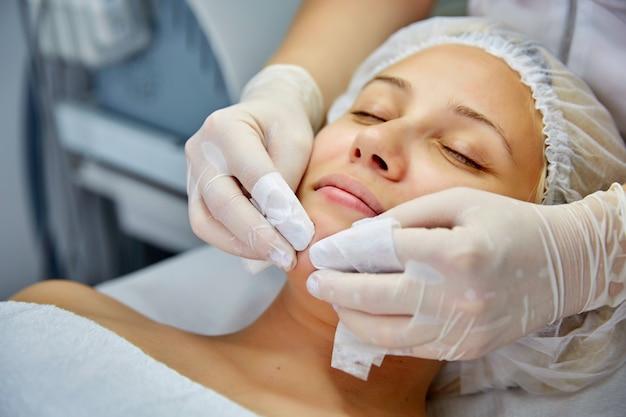 Belle jeune femme recevant un massage facial et un traitement spa.