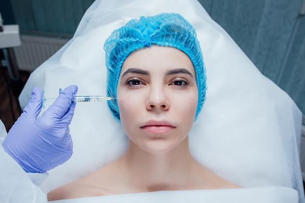 Belle jeune femme reçoit une injection de beauté dans le front du sergent