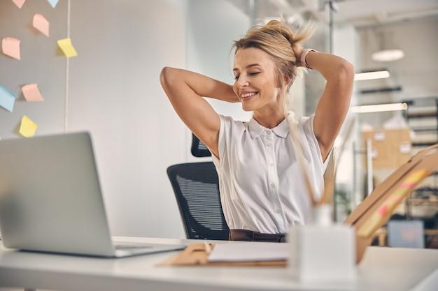 Belle jeune femme regardant l'affichage de l'ordinateur portable et souriant tout en mettant ses cheveux en l'air