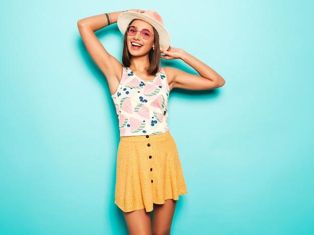 Belle jeune femme regardant la caméra au chapeau. fille à la mode en t-shirt blanc d'été décontracté et jupe jaune à lunettes de soleil rondes. la femelle positive montre des émotions faciales. modèle drôle isolé sur bleu