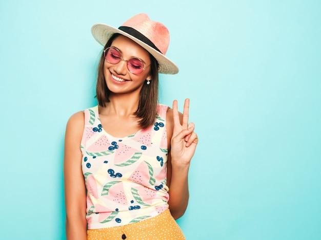 Belle jeune femme regardant la caméra au chapeau. fille à la mode en t-shirt blanc d'été décontracté et jupe jaune à lunettes de soleil rondes. la femelle positive montre des émotions faciales.