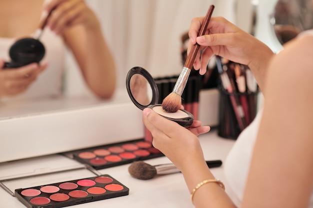 Belle jeune femme regardant dans le miroir et appliquant le cosmétique avec un gros pinceau
