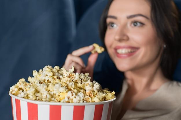 Belle jeune femme en regardant un film au cinéma