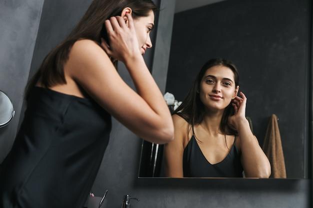 Belle jeune femme regardant le miroir dans la salle de bain le matin