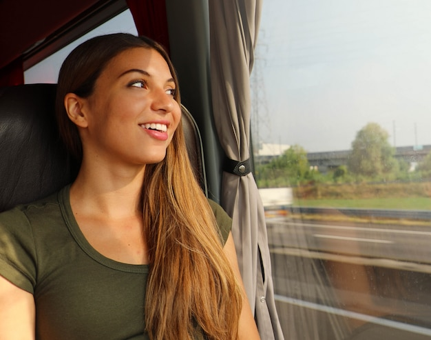 Belle jeune femme regardant à travers la fenêtre du bus. passager de bus heureux voyageant assis sur un siège et regardant par la fenêtre.