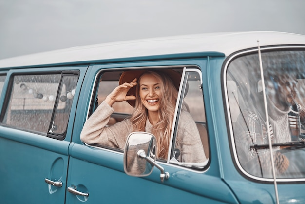 Belle jeune femme regardant à travers une fenêtre et souriant pendant que son petit ami conduit une voiture