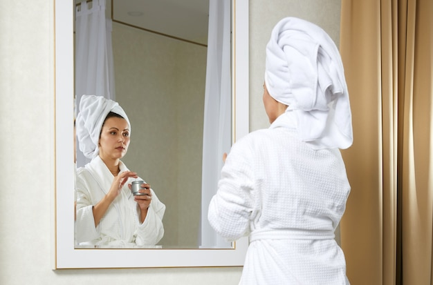 Belle jeune femme regarde dans un miroir en appliquant une serviette enveloppante crème jolie dame sur la tête, met le visage