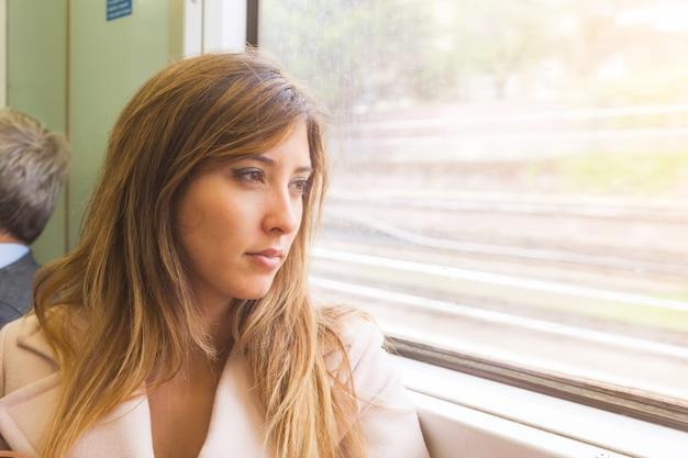 Belle jeune femme regarde par la fenêtre du train