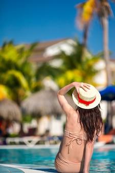 Belle jeune femme relaxante au bord de la piscine infiniti