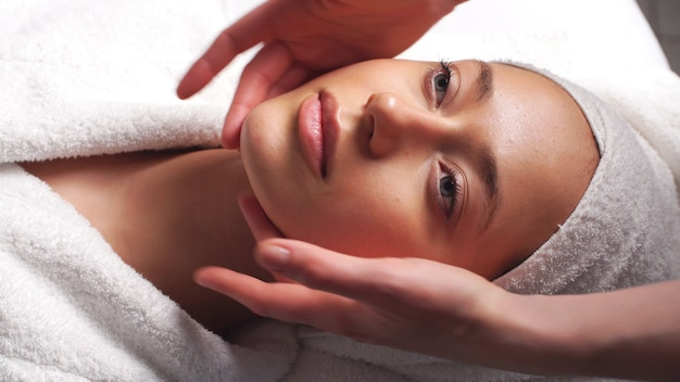 Belle jeune femme relaxante femelle recevant un massage facial du corps beauty spa.