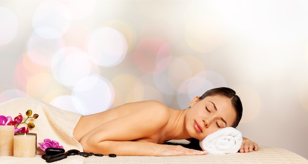 Belle jeune femme relaxante avec massage aux pierres au spa de beauté