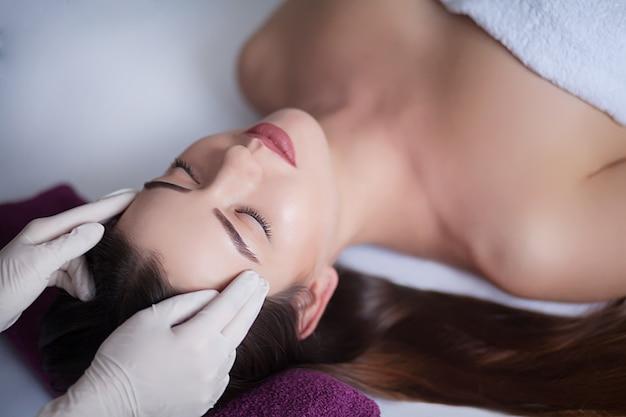 Belle jeune femme relaxante avec massage du visage au spa de beauté.