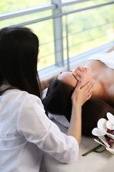 Belle jeune femme relaxante avec massage des mains au spa de beauté