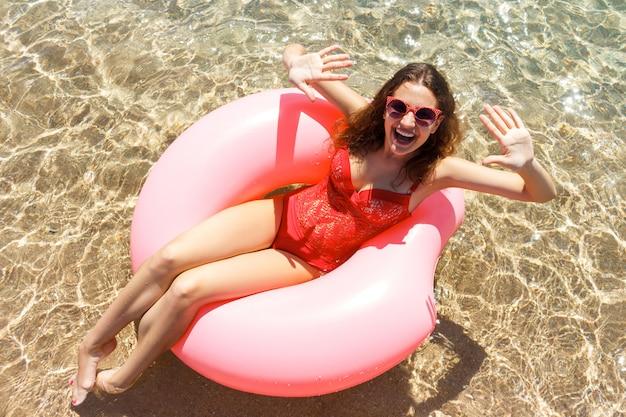 Belle jeune femme reposante sur un beignet gonflable en mer