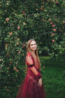 Une belle jeune femme en robe de barde regarde dans les champs et le jardin.