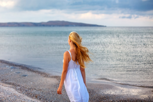 Belle jeune femme en robe blanche au bord de la mer au soleil.