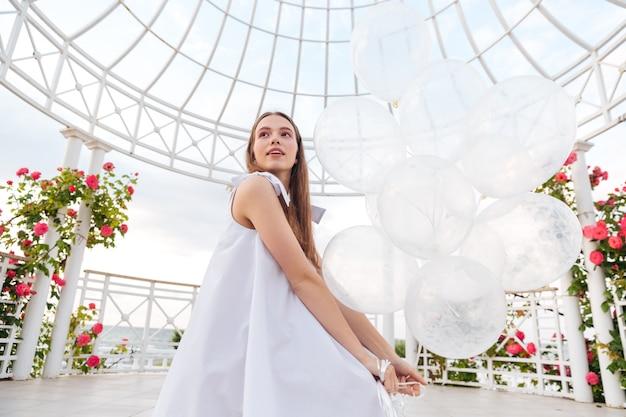 Belle jeune femme en robe blanche avec des ballons sur la terrasse en plein air