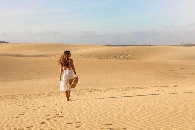 Belle jeune femme avec une robe blanche marchant dans les dunes du désert pendant le coucher du soleil. fille qui marche sur le sable doré sur corralejo dunas, fuerteventura.